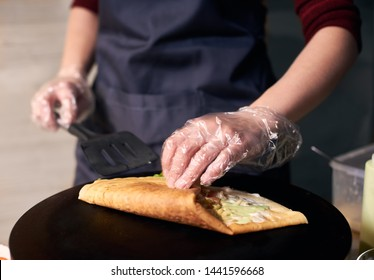 Step-by-step recipe for cooking dish. Chef cooking crepe on hot round cooktop. Skillful hands with black spatula rolling up big crepe greased with sauce. Traditional restaurant healthy food. Close up.
