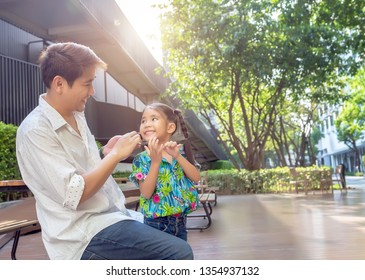 stepfather concept daddy love daugther do pigtail hair for kid at park in morning .Lovely moment of family.