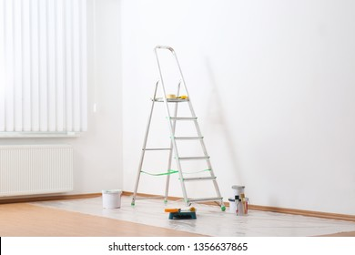Stepladder and painting tools near wall in empty room
