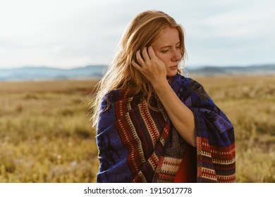 In the steppe against the hills a close-up of a girl straightening blond hair at the temple on her shoulders ethno cape. High quality photo