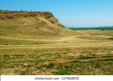 Steppe at the end of May. The entire steppe is covered with last year's dry grass. Young green grass is just starting to grow. The steppe looks yellow with green spots. Khakassia, Russia