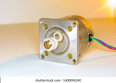 Stepper motor, disassembled, with the rotor set aside .Stepper motor with power cable attached, on white background