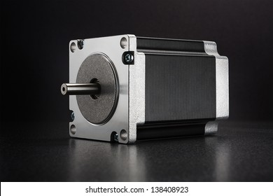 Stepper motor with NEMA standard flange, used for driving linear axes of CNC machines like 3D printers and routers, on dark background with diffused reflection
