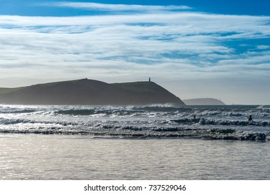 Stepper Point in silhouette from the adjacent Polzeath beach. The headland north of Padstow includes a landmark lookout station with views across Padstow Bay.