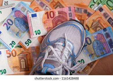 stepping with foot on several hundred euros in banknotes lying on the ground