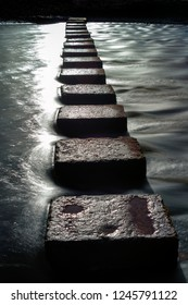 The stepping stones that allow access over the river to the divided beaches at Three Cliffs Bay on the Gower peninsula in Swansea, South Wales, UK