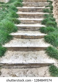 Steps covered in sand with grass