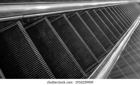 steps of the escalator in black and white