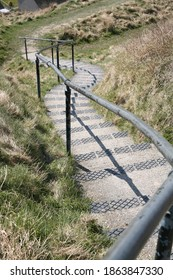 Steps and a hand rail going down a grassy hill
