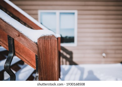Steps leading to a wooden deck of a residential house with snow during the winter