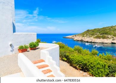 Escaleras a la tradicional casa blanca y vistas a los barcos pesqueros en el mar en la bahía de Cala Portinatx, Ibiza isla, España