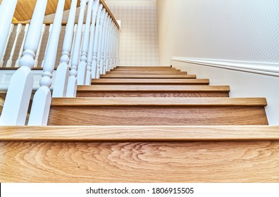 Steps of a wooden staircase with white balusters and pillar. Bottom view