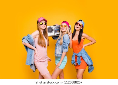Stereo fan song sound audio cassette tape hip-hop old school lover portable culture concept. Portrait of funky trio gesturing peace symbol having rest relax isolated on vivid yellow background