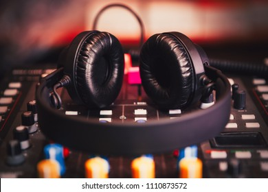 Stereo head set for playing music loud.Professional club dj headphones & sound mixer on concert stage.Disc jockey technology for mixing musical tracks on party in nightclub.