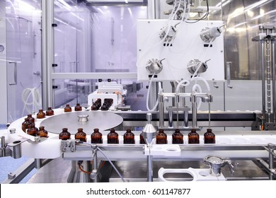 Sterile bottles and ampoules on the dispensing line. Sealed ampoules with medicine. Sterile capsules for injection Bottles on the bottling line of the pharmaceutical plant. Machine after checking.