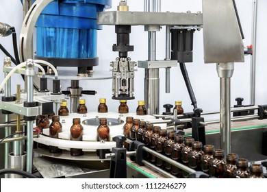 Sterile bottles on the production line conveyor of the pharmaceutical industry. Machine for liquid drugs glassware bottling.
