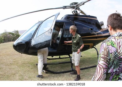 Sterkrivier Limpopo South Africa 10102010 people tourists boarding black helicopter with help of rangers