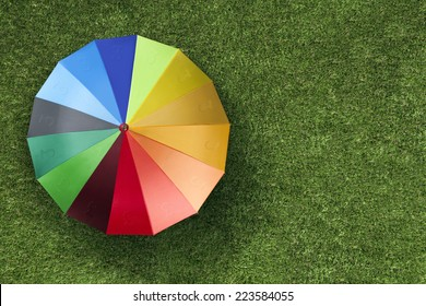 Sterling currency units on colorful umbrella on green grass
