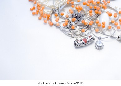 Sterling Silver jewelry with coral on a white background, pearls