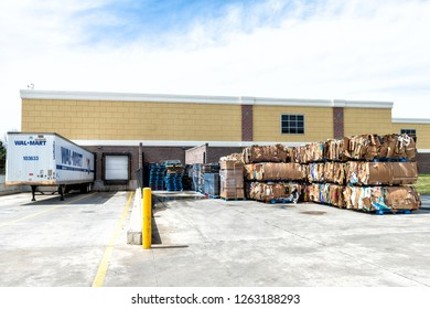 Sterling, USA - April 4, 2018: Walmart, Wal-mart semi truck trailer tractor loading dock station, container with stacks, piles of many stacked, compressed cardboard boxes by store, shop