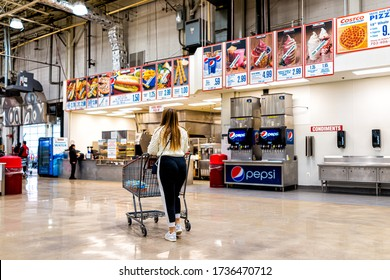 Sterling, USA - March 23, 2020: People customers woman walking to exit in Costco discount membership club store during Coronavirus Covid-19 outbreak with empty food court