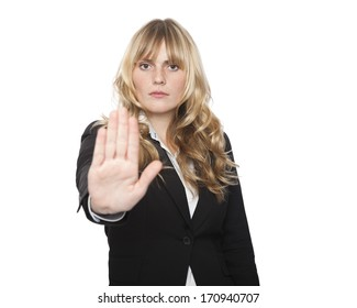 Stern attractive blond businesswoman making a stop gesture with her hand with the palm forward to show that entry is forbidden or to call a halt as a time deadline expires