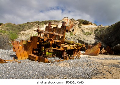 From stern to bow, an almost destroyed pusher boat wrecked, rusted and half buried at the beach sand. Vila Nova de Milfontes, Portugal.