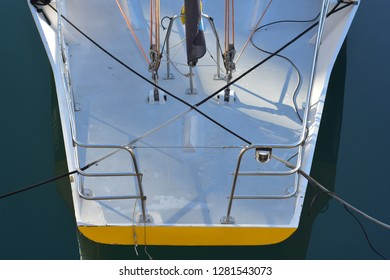 Stern of composite racing sailing ship with stainless steel pushpit and some rigging visible. Craft is berthed in marina with absolutely still water.