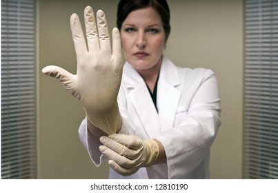 Stern Doctor Pulling on a Rubber Glove