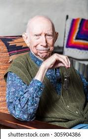 Stern elder gentleman sitting on chair in livingroom
