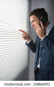 Stern handsome businessman looking through roller blind phoning in dark room