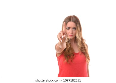 Stern implacable young woman saying no and gesturing with her finger to emphasise her point isolated on a white studio background