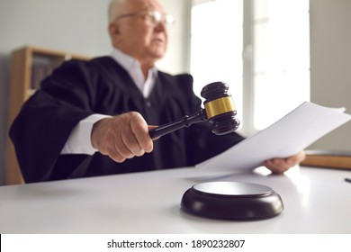 Stern judge with paper document pronouncing sentence in a court of law. Judge finds the accused guilty, passes judgement and rules case closed. Hand holding gavel and hitting sound block in close-up