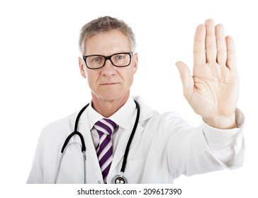 Stern middle-aged male doctor holding up his hand in a Halt or Stop gesture as he signals he has had enough, or denies access or tells someone to go away, isolated on white