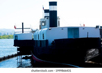 The stern of an old ship near the bank of the city embankment. An old ship with a steam engine.