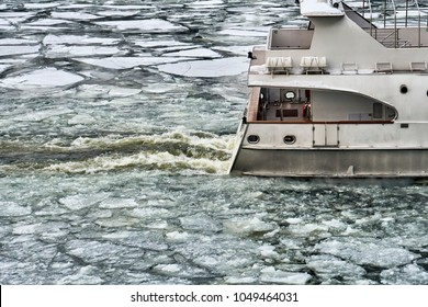 Stern of ship sailing along a river covered with ice floes in early spring.