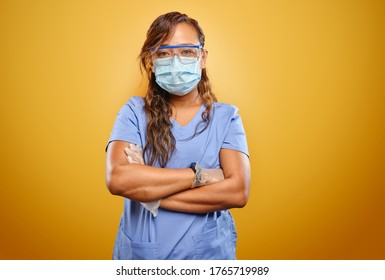 stern and strong filipina nurse with arms crossed wearing PPE