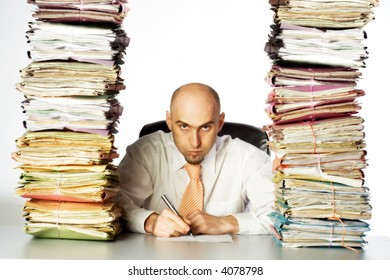 A stern and unpleasant administrative clerk glares through two huge stacks of business files, clearly indicating he has not time or desire to be of any customer service.