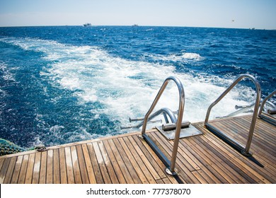 stern of a yacht with boarding ladder on a background of azure sea. amazing vacation. travelling . luxury life