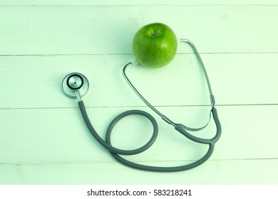stethoscope and apple on wooden background