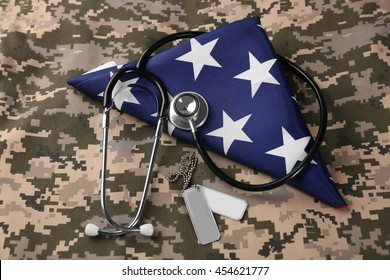 Stethoscope and army token on American flag and khaki background