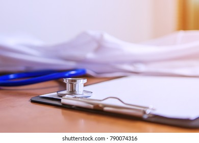Stethoscope with blank clipboard on desk in hospital / copy space