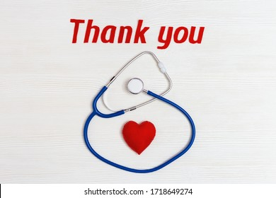 "Stethoscope blue colored, red heart and text ""thank you"" on white wooden background with copy space. Healthcare and medical concept. World health day. View from above."