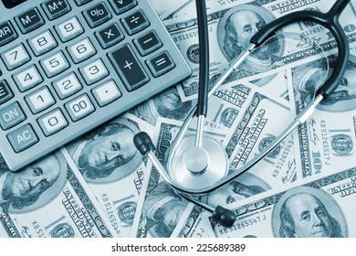 Stethoscope and calculator on banknotes, cost of healthcare concept