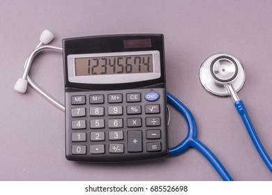 Stethoscope and calculator on a gray background. Dear medicine or medical insurant