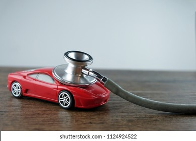 Stethoscope and car on the wooden table, Concept of car check-up, repair and maintenance.
