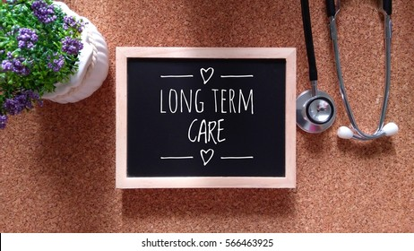 Stethoscope, Chalk board and flower with inscription long term care on a wooden table. Medical and health care concept.