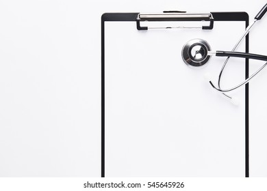 Stethoscope and clipboard with blank white sheet of paper and copy space