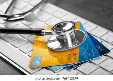 Stethoscope and credit cards on computer keyboard, closeup