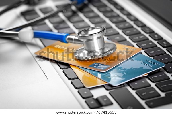 Stethoscope and credit cards on laptop keyboard, closeup
